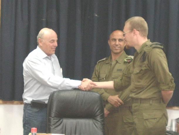 נשיא המרכז האקדמי פרופ' נחום ביגר מעניק שי לחייל בודד. באמצע – מפקד העוצבה